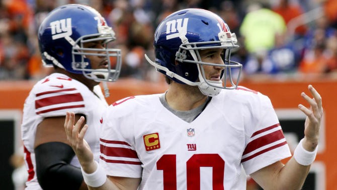 New York Giants quarterback Eli Manning (10) holds up his hands after having a pass tipped for an interception in the second half of an NFL football game against the Cincinnati Bengals, Sunday, Nov. 11, 2012, in Cincinnati. (AP Photo/Tom Uhlman)
