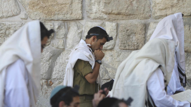 In this Monday, July 2, 2012 an Israeli soldier prays next to the Western Wall, the holiest site where Jews can pray, in Jerusalem's Old City. Deep in the heart of Mea Shearim, a Jerusalem bastion of hardline ultra-Orthodox Jews, hundreds of bearded young men in black suits have their noses burrowed into books, immersed in biblical study and oblivious to their surroundings. These young men, and their sheltered lifestyle, are at the heart of a battle that is tearing Israel apart in a clash between tradition and modernity, religion and democracy. The fight centers on whether ultra-Orthodox males should be drafted into the military along with other Jews, but it really is about a much deeper issue: the place of Judaism in the Jewish state. Deep in the heart of Mea Shearim, a Jerusalem bastion of hardline ultra-Orthodox Jews, hundreds of bearded young men in black suits have their noses burrowed into books, immersed in biblical study and oblivious to their surroundings. These young men, and their sheltered lifestyle, are at the heart of a battle that is tearing Israel apart in a clash between tradition and modernity, religion and democracy. The fight centers on whether ultra-Orthodox males should be drafted into the military along with other Jews, but it really is about a much deeper issue: the place of Judaism in the Jewish state. (AP Photo/Dan Balilty)