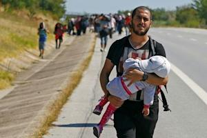 A Syrian migrant carries a baby as he walks towards …