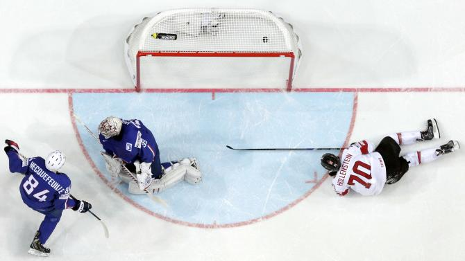 Switzerland's Hollenstein scores a goal past France's goaltender Huet and Hecquefeuille during their Ice Hockey World Championship game at the O2 arena in Prague