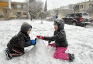 Children play in the snow in the Montenegrin capital Podgorica, Tuesday, Dec. 11, 2012. Heavy snowfall in blizzards have closed roads, disrupted power supplies and shut down an airport in Montenegro, amid a winter freeze that has killed several people and created travel chaos in the Balkans since last weekend.(AP Photo/Risto Bozovic)