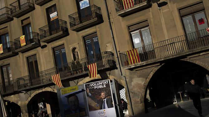 "In this photo taken on Saturday, Nov. 10, 2012, an electoral poster of the leader of center-right Catalan Nationalist Coalition (CiU) Artur Mas is seen next to balconies adorned with pro-independence ""estelada"" flags and also ""senyeras"" Catalan flags in Vic, a town declared by the city council a ""free Catalan territory"" in Spain. Catalonia holds elections on Sunday that will be seen as a test of the regional government's plans to hold a referendum on independence, and one of the key issues emerging is the theoretical place of a free Catalonia in Europe. (AP Photo/Emilio Morenatti)"