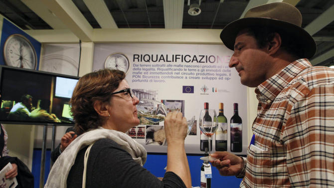 """Marcio Alexandre Alberto, a Brazilian sommelier, right, is flanked by an unidentified woman tasting a glass of white wine in a 'Pon sicurezza project' stand at the 46th edition of the annual International Wine and Spirits Exhibition """"Vinitaly"""", in Verona, northern Italy, Monday, March 26, 2012. The wine exhibition runs until March 28.  (AP Photo/Luca Bruno)"""