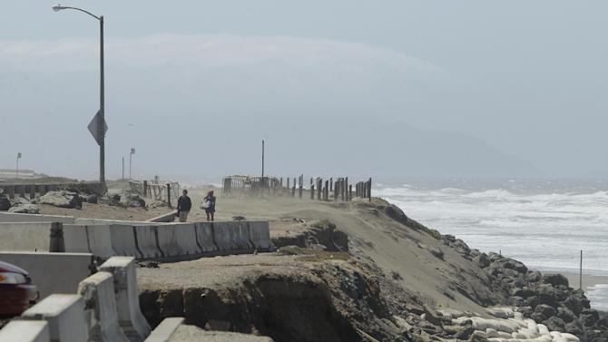 In this photo from Thursday, May 24, 2012, a man and woman walk in the parking lot at Ocean Beach in San Francisco. In San Francisco, officials are mulling a significant retreat on its western flank, where the Great Highway is under assault from the Pacific Ocean. Right now, a beach parking lot that abuts the highway is crumbing into the sea just across the highway from the San Francisco Zoo. (AP Photo/Jeff Chiu)