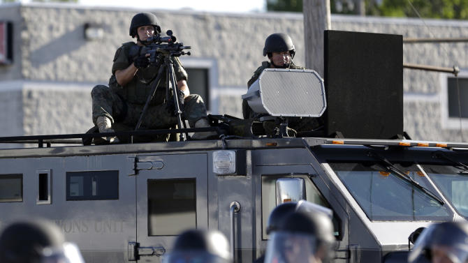 A police tactical team moves in to disperse a group of protesters on Wednesday, Aug. 13, 2014, in Ferguson, Mo. The protests were sparked after Michael Brown, an unarmed black man, was shot and killed by Darren Wilson, a white Ferguson police officer, on Aug. 9, 2014. (AP Photo/Jeff Roberson)