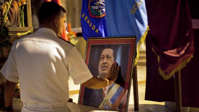 FILE - In this Thursday, Dec. 13, 2012 file photo, a member of Venezuela's navy touches an image of Venezuela's President Hugo Chavez after a mass in support of him in Havana, Cuba. Venezuelan Vice President Nicolas Maduro said late Monday, Dec. 24, 2012 night that he had spoken by telephone with Chavez and that the leader is up and walking following cancer surgery in Cuba. (AP Photo/Ramon Espinosa)