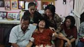 Risman Siregar (L) comforts his wife Erlina Panjaitan (C), parents of Firman Chandra Siregar, a 24 year-old passenger of Malaysia Airlines flight 370 that went missing on March 8, in Medan on March 9, 2014