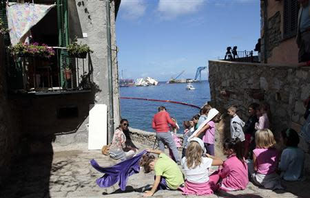 "Children look on at the capsized Costa Concordia cruise liner after the start of the ""parbuckling"" operation outside Giglio harbour"