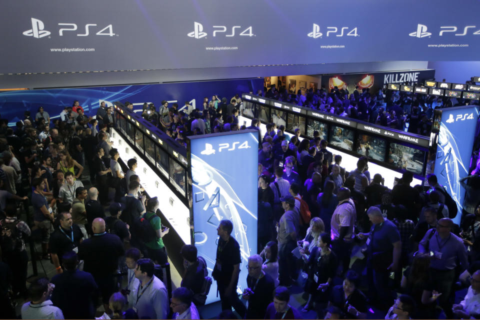 Show attendees play video games on the new Sony PlayStation 4 at the Sony booth during the Electronic Entertainment Expo, in Los Angeles, Tuesday, June 11, 2013. (AP Photo/Jae C. Hong)