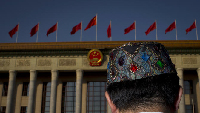 In this Thursday, Nov. 8, 2012 photo, a Communist Party delegate in a traditional Uighur ethnic minority dress walks to the Great Hall of the People, where the opening session of the 18th Communist Party Congress is held in Beijing. Along with government officials, managers of state industries and military officers, delegates of the 18th Communist Party Congress also include migrant workers, peasants, factory technicians, teachers, doctors, artists and Olympic gold medalists. Many of the rank and file delegates are brought to Beijing to make the roughly 2,300-member congress more representative, and have no real political clout. They ratify decisions made by a few dozen party insiders in backroom deals. Still, they believe in the cause and swoon at the prestige of being chosen to be a national delegate. (AP Photo/Alexander F. Yuan)