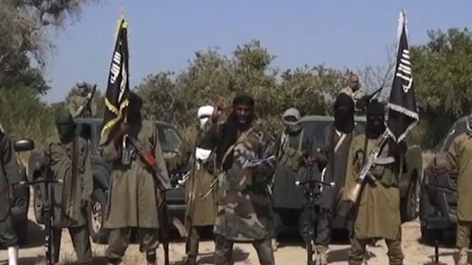 An image grab made on October 31, 2014 from a video from Islamist extremist group Boko Haram shows the group's leader Abubakar Shekau (C) delivering a speech