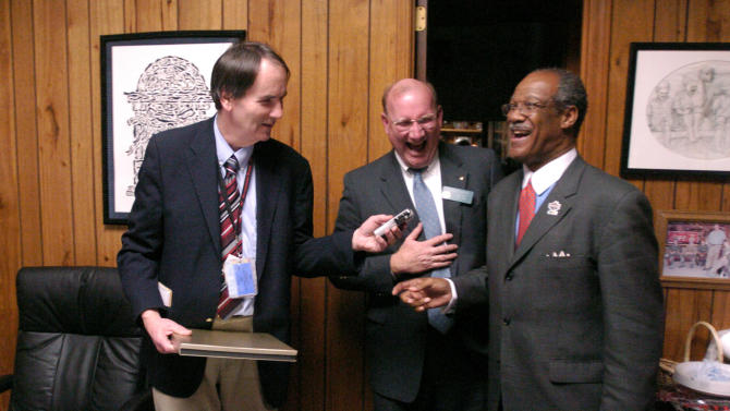 In a Monday Feb. 2, 2004 photo, Associated Press staff writer Dick Pettys, left, jokingly holds up a recorder to get offhand comments, to the laughter of  House Speaker Pro Tempore Dubose Porter, center, and Majority Caucus Chairman Calvin Smyre, during a  celebration of his 35 years with AP covering the State House, pictured after the general session at the capitol in Atlanta. Pettys, who was a fixture at the Georgia state Capitol for more than three decades and a well-respected mentor to other journalists, died Monday, Oct. 8, 2012 following a massive heart attack at his north Georgia home. He was 66. (AP Photo/John Amis)