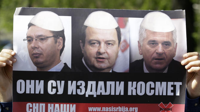 """A protester holds a poster depicting, from left: Serbian Progressive Party leader and deputy Prime Minister Aleksandar Vucic, Serbian Prime Minister Ivica Dacic and Serbia's President Tomislav Nikolic, that reads: """"They Betrayed Kosovo"""" during a rally in front of Serbia's parliament building in Belgrade, Serbia, Friday, April 26, 2013. Serbian lawmakers are debating an EU-brokered deal on normalization of ties with breakaway Kosovo which was signed by the government and sets the former war foes on the path of reconciliation and EU integration. (AP Photo/Darko Vojinovic)"""