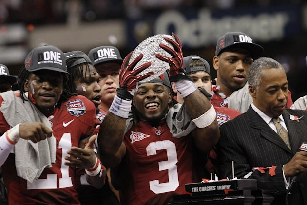 FILE - In this Jan. 9, 2012, file photo, Alabama running back Trent Richardson holds up the championship trophy after winning the BCS National Championship NCAA college football game against LSU, in N