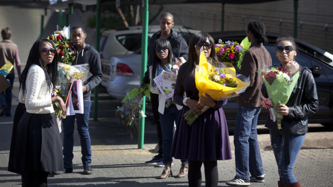 Granddaughter Ndileka Mandela, center right, with other relatives carry bunches of flowers that were left by wellwishers into the Mediclinic Heart Hospital where former South African President Nelson Mandela is being treated in Pretoria, South Africa Thursday, June 27, 2013. President Jacob Zuma canceled a trip to Mozambique on Thursday in an indication of heightened concern about Mandela, whose health deteriorated last weekend. (AP Photo/Ben Curtis)