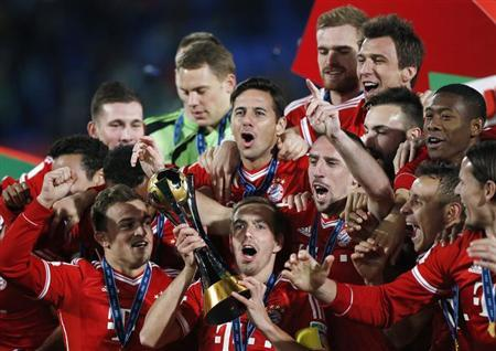 Germany's Bayern Munich Philipp Lahm (bottom C) holds the trophy as he celebrates with his teammates after winning their 2013 FIFA Club World Cup final soccer match against Morocco's Raja Casa