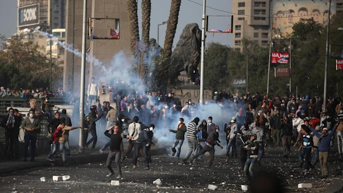 Egyptian protesters clash with riot police, not seen, near Tahrir Square, Cairo, Egypt, Tuesday, Jan. 29, 2013. Intense fighting for days around central Tahrir Square engulfed two landmark hotels and forced the U.S. Embassy to suspend public services on Tuesday. (AP Photo/Khalil Hamra)