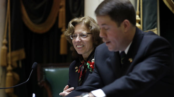 In this Tuesday, March 19, 2013 photo Rhode Island Senate President Teresa Paiva Weed, left, and her Chief of Staff Tom Coderre, right, confer at the rostrum in the Senate Chamber at the Statehouse, in Providence, R.I. Paiva Weed said she intends to vote against gay marriage legislation in the Rhode Island Senate Wednesday. (AP Photo/Steven Senne)