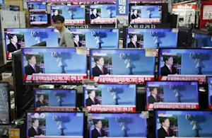 A sales assistant watches TV sets broadcasting a news report on North Korea's nuclear test, in Seoul