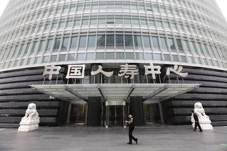 A man walks in front of China Life headquarters building at Beijing's Financial Street