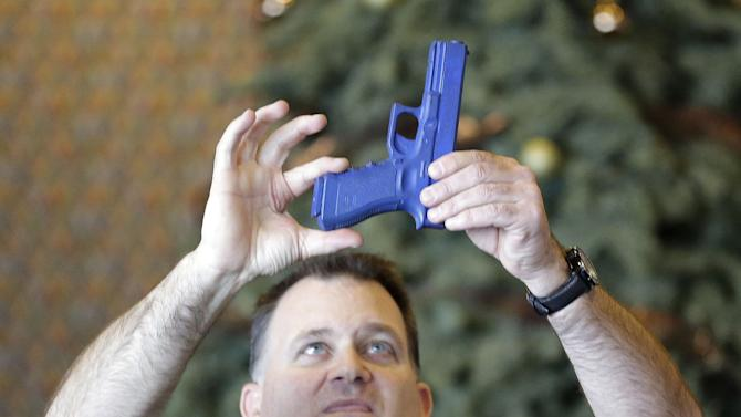 Clark Aposhian, President of Utah Shooting Sport Council, demonstrates with a plastic gun during concealed-weapons training for 200 Utah teachers Thursday, Dec. 27, 2012, in West Valley City, Utah. The Utah Shooting Sports Council offered six hours of training in handling concealed weapons in the latest effort to arm teachers to confront school assailants. (AP Photo/Rick Bowmer)