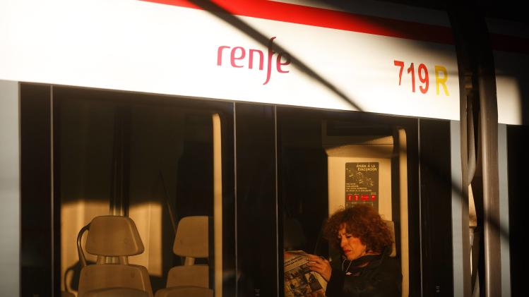A commuter reads a newspaper on a train at Atocha train station on the tenth anniversary of the Madrid train bombings