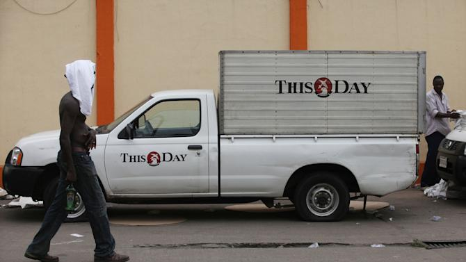 A member of staff from  This Day newspaper walks past a delivery van as workers barricaded the office due to non payment of salaries  in Lagos, Nigeria, Friday, May 10, 2013. Known more for bringing in celebrities and smiling in photographs next to former Western leaders, a flamboyant Nigerian newspaper publisher now faces a challenge from his most vocal critics _ his own employees. Workers have barricaded the front of This Day newspapers in Lagos, hoping to force publisher Nduka Obaigbena into paying them as much as four months' worth of back salaries due to them. Back pay disputes often hit industries in Nigeria, a country where steady paying jobs remain few, but this crisis has hit a man politically connected to the nation's ruling elite, the second such major business figure to be stung in recent months. (AP Photos/Sunday Alamba)