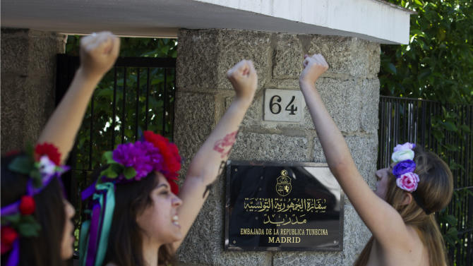 Activists of FEMEN shout for the release of fellow activists, who are imprisoned in Tunisia during a protest outside the Tunisian embassy in Madrid, Spain Wednesday June 12, 2013. (AP Photo/Paul White)