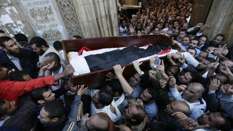 """Muslim Brotherhood and Egyptian President Morsi supporters carry a body of one of six victims who were killed during Wednesday's clashes during their funeral outside Al Azhar mosque, the highest Islamic Sunni institution, Friday, Dec. 7, 2012. During the funeral, thousands Islamist mourners chanted, """"with blood and soul, we redeem Islam,"""" pumping their fists in the air. """"Egypt is Islamic, it will not be secular, it will not be liberal,"""" they chanted as they walked in a funeral procession that filled streets around Al-Azhar mosque. Thousands of Egyptians took to the streets after Friday midday prayers in rival rallies and marches across Cairo, as the standoff deepened over what opponents call the Islamist president's power grab, raising the specter of more violence. (AP Photo/Hassan Ammar)"""