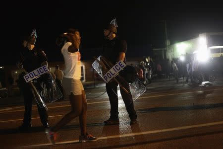 A demonstrator protesting the shooting death of Michael Brown, holds her hands in the air as she walks past police officers in riot gear, in Ferguson, Missouri