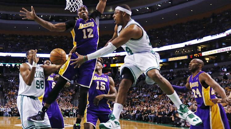 Boston Celtics forward Paul Pierce (34) dumps off the ball to center Jason Collins (98) as he is pressured by Los Angeles Lakers center Dwight Howard (12) during the first quarter of an NBA basketball game in Boston, Thursday, Feb. 7, 2013. At right is Lakers guard Kobe Bryant (24). (AP Photo/Charles Krupa)