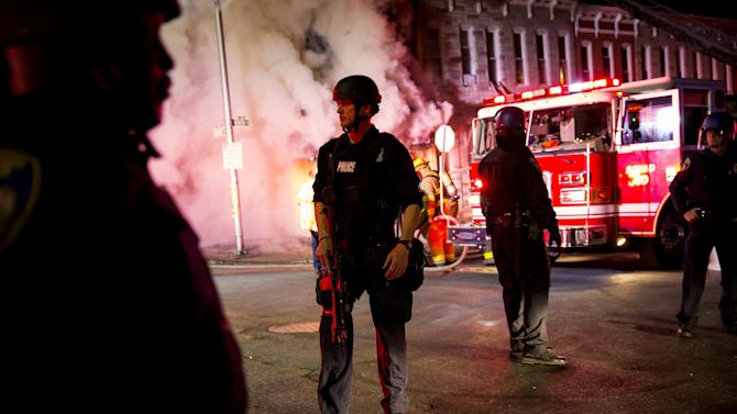 Police stand nearby as firefighters attack a fire in a convenience store and residence during clashes after the funeral of Freddie Gray in Baltimore, Maryland
