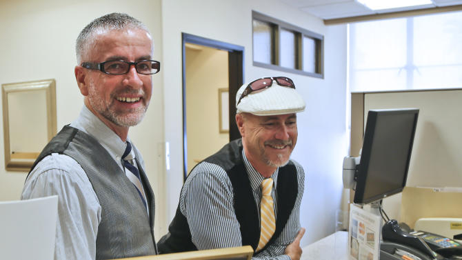 Bruce Fox, right, and Colum O'Hare apply for their marriage license in the San Diego County offices where they learned the the schedule for actual marriage ceremonies is booked through the week in San Diego, Monday, July 1, 2013. The couple said they have been together for 15 years. (AP Photo/Lenny Ignelzi)