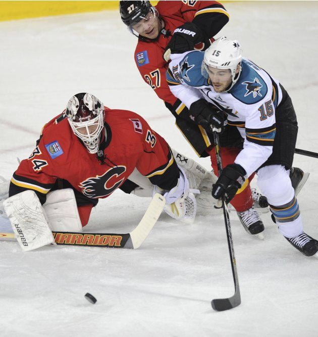Calgary Flames' Miikka Kiprusoff  makes a dive against San Jose Sharks' James Sheppard  who is being checked by Flames' Derek Smith during the first period of their NHL hockey game in Calgary