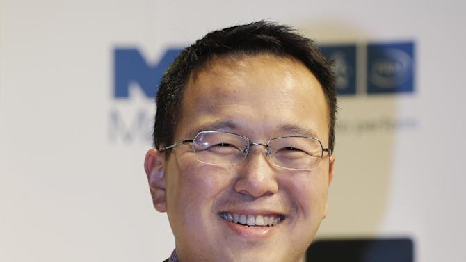 Author Tan Twan Eng, of Malaysia, shortlisted for the Man Booker Prize, holds a copy of his book 'The Garden of Evening Mists', during a photo call at the Royal Festival Hall, in London, Monday Oct. 15, 2012.  The 50,000 British pounds (US 80,000 dlrs) prize will be announced Tuesday, Oct. 16, 2012. (AP Photo/Lefteris Pitarakis)