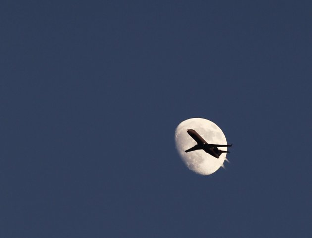 An airplane passes by the moon in its waxing gibbous phase in the sky over Hoboken
