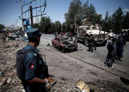 An Afghan policeman keeps watch at the site of a suicide bomb attack in Kabul, Afghanistan