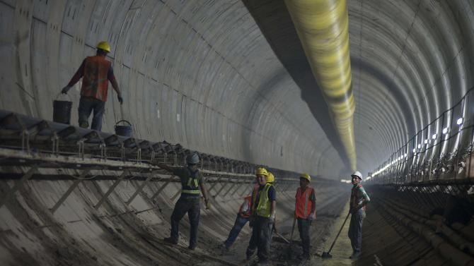 In this Aug. 19, 2014 photo, workers shovel ground rock, left by the giant boring machine, to a conveyer belt inside the Tunel Emisor Oriente in Zumpango, Mexico. Scheduled to be completed by 2018, a decade after it was begun, the 62 kilometer (38 mile) tunnel will be the largest sewer in Latin America. (AP Photo/Sean Havey)