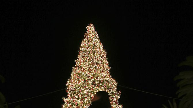 In this Thursday, Dec. 20, 2012, photo, a holiday shopper walks past a large Christmas tree at Fashion Island shopping center in Newport Beach, Calif. U.S. holiday retail sales this year are the weakest since 2008, after a shopping season disrupted by storms and rising uncertainty among consumers. A report out Tuesday that tracks spending, called MasterCard Advisors SpendingPulse, says holiday sales increased 0.7 percent. Analysts had expected sales to grow 3 to 4 percent. (AP Photo/Chris Carlson)