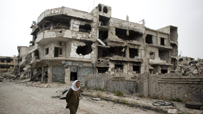 In this June 5, 2014 photo, a woman walks through a devastated part of Homs, Syria. Syrian government forces retook the control of Homs in May 2014, after a three year battle with rebels. (AP Photo/Dusan Vranic)