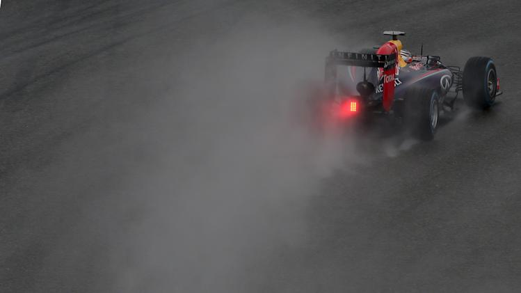 Red Bull Racing driver Sebastian Vettel of Germany drives in the rain during the qualifying session of the Chinese Formula One Grand Prix at Shanghai International Circuit in Shanghai, Saturday, April 19, 2014. Vettel takes third position for Sunday's Chinese Formula One Grand Prix race. (AP Photo/Eugene Hoshiko)