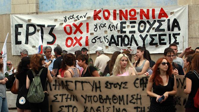"""Workers protest outside the Greek state television ERT 3 headquarters after the government's decision to shut down the broadcaster in Thessaloniki, on Thursday, June 12, 2013. State TV and radio signals were cut early Wednesday, hours after the government closed the Hellenic Broadcasting Corp., ERT, and fired its 2,500 workers. Banner reads """"No to the lay offs"""" and """"solidarity to the workers"""". (AP Photo/Nikolas Giakoumidis)"""