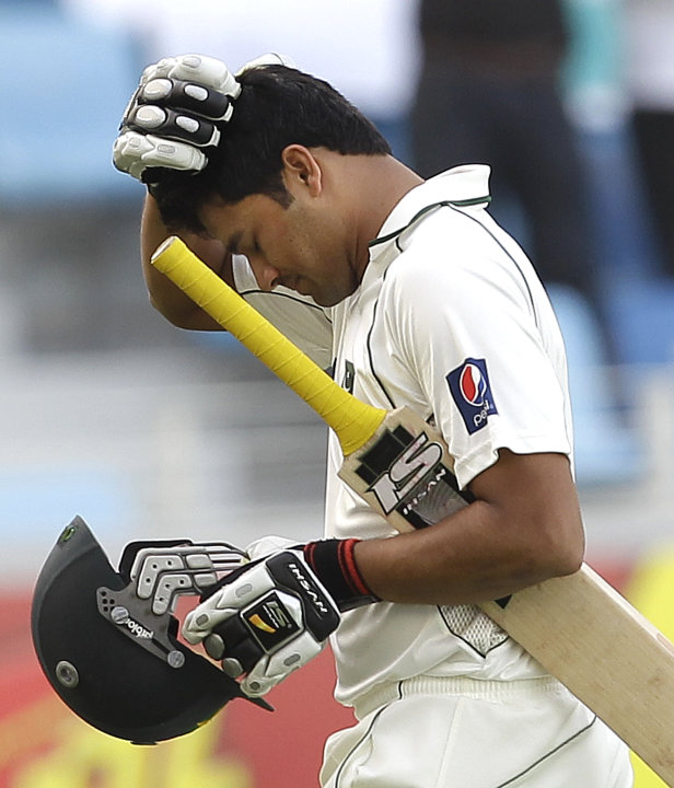 Pakistan's Azhar Ali reacts as walks off the field of play after losing his wicket to England's Graeme Swann during the third day of the third cricket test match of a three match series between Englan