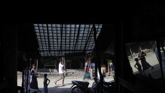 People are reflected in the mirror as they walk past a barber shop in Maungdaw town in northern Rakhine State