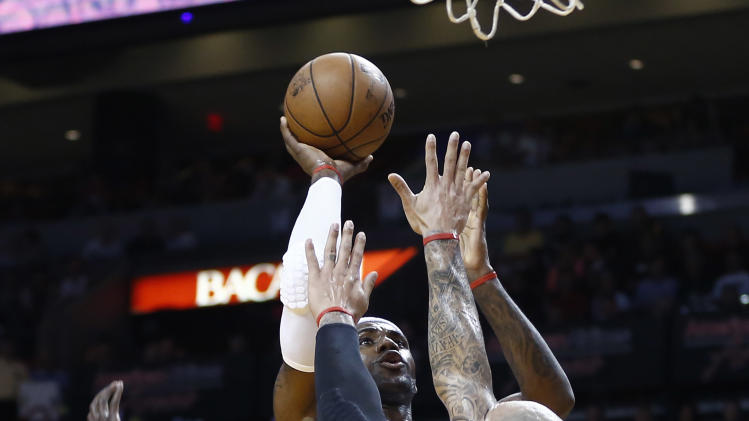 Miami Heat's LeBron James (6) slides in between Chicago Bulls players Carlos Boozer (5) and Luoi Deng (9) for a two point shot during the first half of a NBA basketball game in Miami, Friday, Jan. 4, 2013. (AP Photo/J Pat Carter)