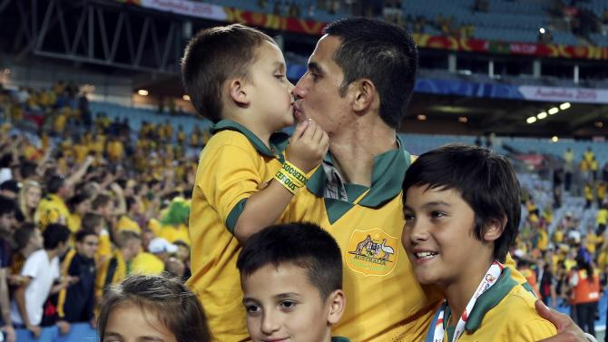 Australia's Tim Cahill poses with his children after they beat South Korea to win the Asian Cup at the Stadium Australia in Sydney