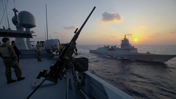"A crew member of the Danish warship Esbern Snare looks at the Norwegian warship ""Helge Ingstad"" as they pass each other during a sunset at sea between Cyprus and Syria, Sunday, Jan. 5, 2014. Two cargo ships and their warship escorts set sail at waters near Syria where they will wait for orders on when they can head to the Syrian port of Latakia to pick up more than 1,000 tons of chemical agents. (AP Photo/Petros Karadjias)"