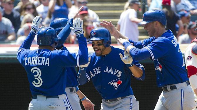 Toronto Blue Jays' Devon Travis, center, is greeted by teammates Ezequiel Carrera (3), Michael Saunders, right, after hitting a grand slam, against the Cleveland Indians during a baseball game in Cleveland, Sunday, May 3, 2015. (AP Photo/Phil Long)