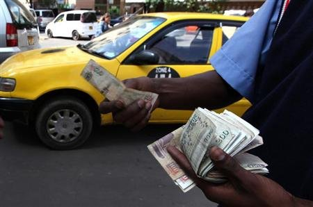 A fuel attendant handles Kenyan shilling notes at a petrol station in the capital Nairobi March 15, 2011. REUTERS/Noor Khamis