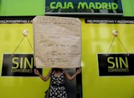"<p>A woman holds a placard reading ""People are starving"" during a demonstration in front of a Bankia office in Sevilla, June 2012. Spain deserves European Union support and has the right to ask for a bailout to unlock required finances over the next two-to-three years, OECD chief Angel Gurria said.</p>"